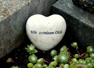 Wir vermissen dich - Inschrift auf einem Herz